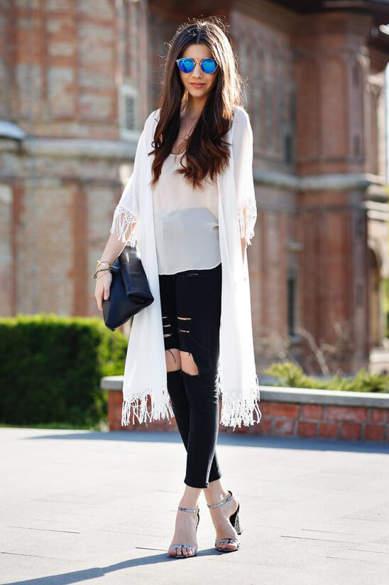 Edgy brunette wearing black ripped jeans and a white silk chiffon kimono. Soften the edgy effect of ripped jeans with layered silk chiffon.