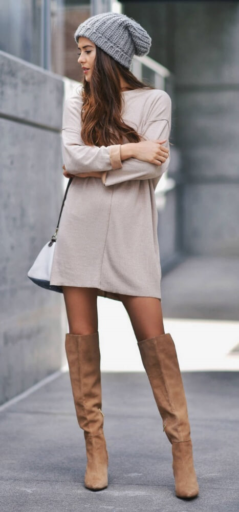 Trendy brunette is wearing a nude woolen sweater dress and brown over-the-knee suede boots. Winter's favorite woolen dress works just as well in the in-between seasons.