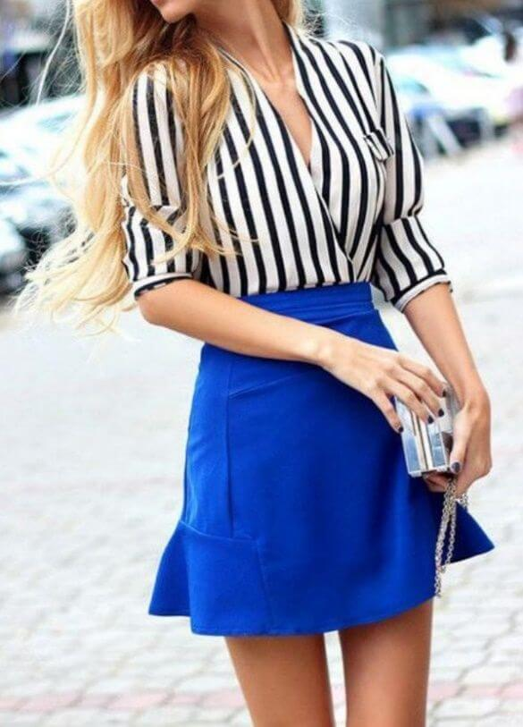 Chic blonde woman in royal blue skirt and striped shirt. You'll be sure to turn heads in solid stripes and bold blue.