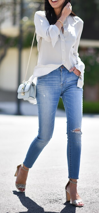 Chic brunette is wearing ripped skinny jeans and a white silk button-down blouse. Classic and cool, this pairing will stay eternally stylish.