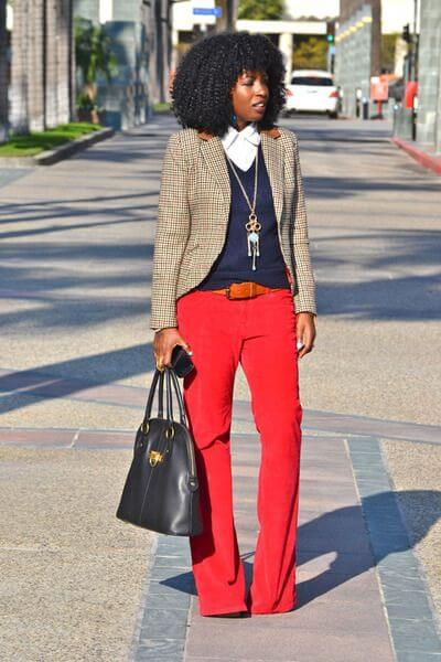 Curly hair lady with wide legs pants, thin sweater, and bright tartan blazer. Spring-safe look to love.
