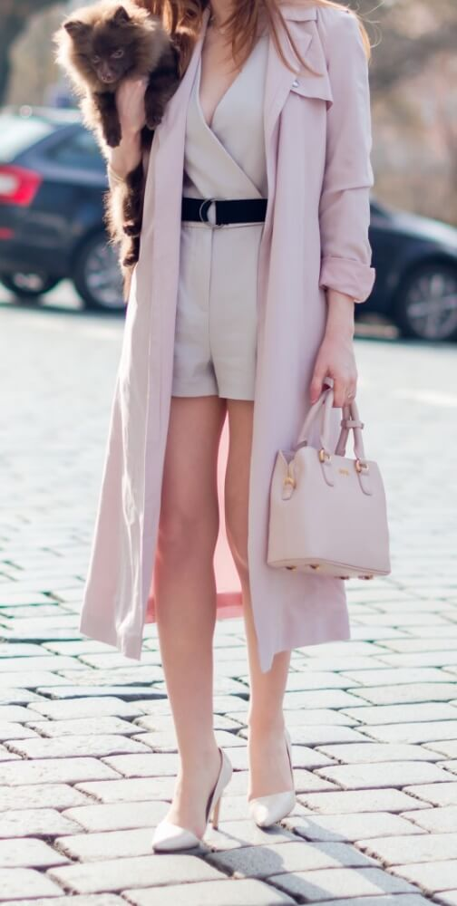 Elegant brunette is wearing a nude-colored playsuit and pale pink duster jacket. Revel in the pastel shades of spring in a soft duster jacket over a cheeky nude playsuit.