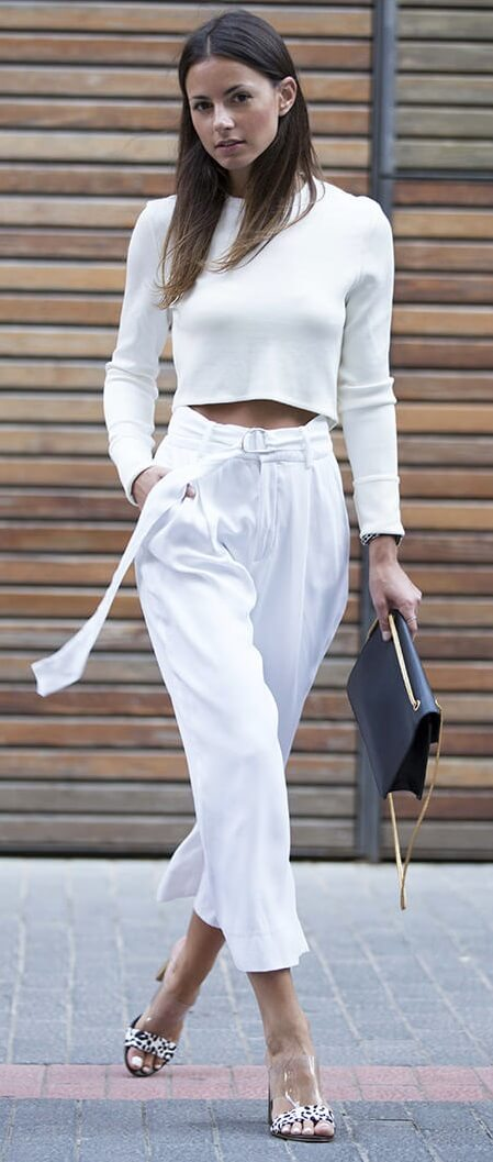 Elegant brunette on the street is wearing white high-waisted palazzo pants and a white crop top. When all else fails, go with classic, crisp white to make a lasting impression.