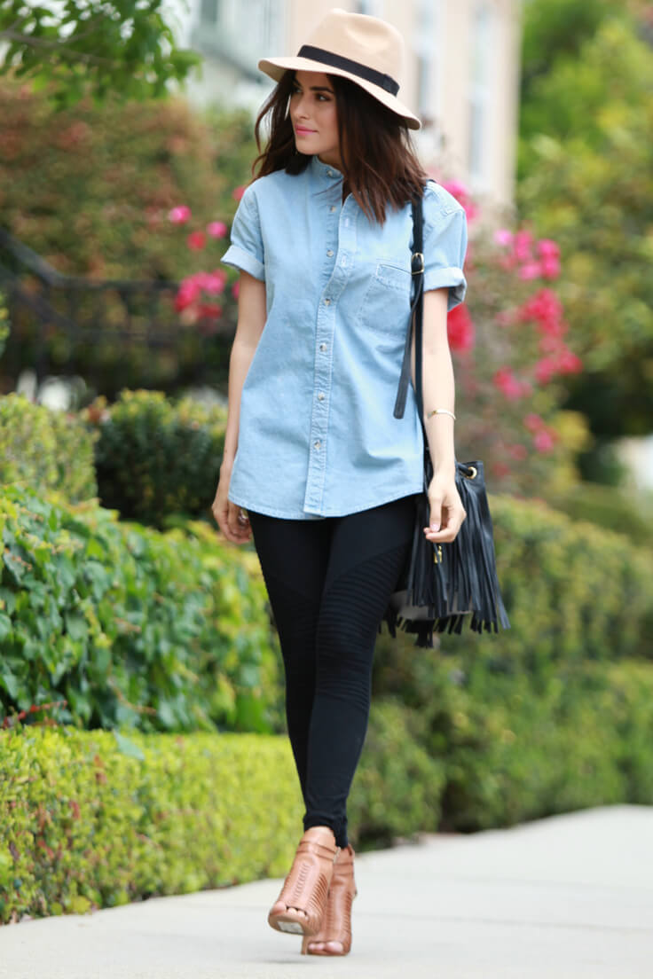 Trendy girl in black leggings and a denim chambray shirt. The classic meeting between blue denim and basic black works a charm every time.