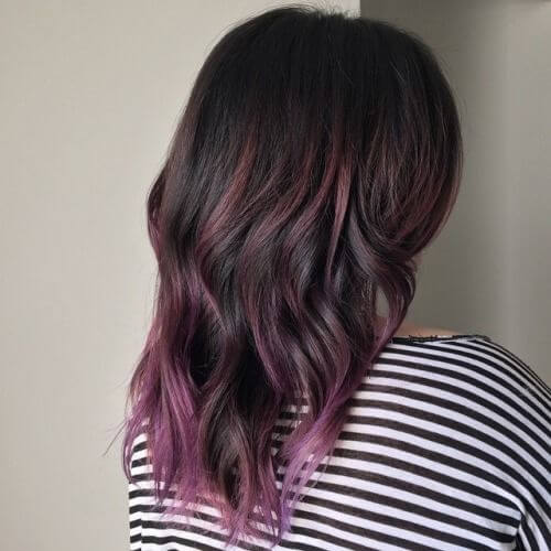 A pop of pink is way more low-maintenance than a full head of pink hair. Magenta accents have been added to the ends of this woman's natural brown hair.