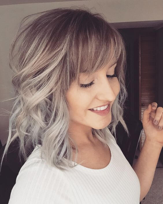 Add some interest to your hair by using gray tones. In this hairstyle, side-swept bangs and a short gray ombre create a light and springy 'do.