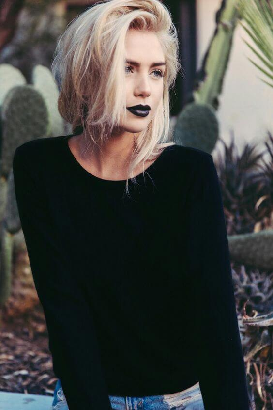 "There's no such thing as ""too blonde."" This model posing in a black top and ripped jeans has her hair tied back and has paired her platinum hair with contrasting black lipstick."