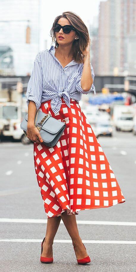 Stylish brunette in check midi skirt and striped shirt. Contrast is king when thin stripes meet a bold check print.