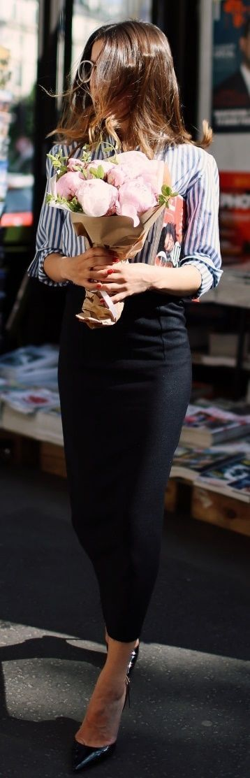 Stylish brunette in long black pencil skirt and striped shirt. An office look gets glammed up with basic stripes and a sleek pencil skirt.