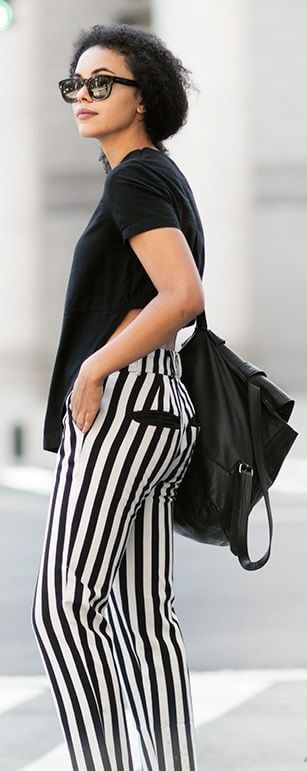 Stylish woman in striped pants and black cotton T-shirt. Solid black and white stripes are cool and edgy for comfortable city living.