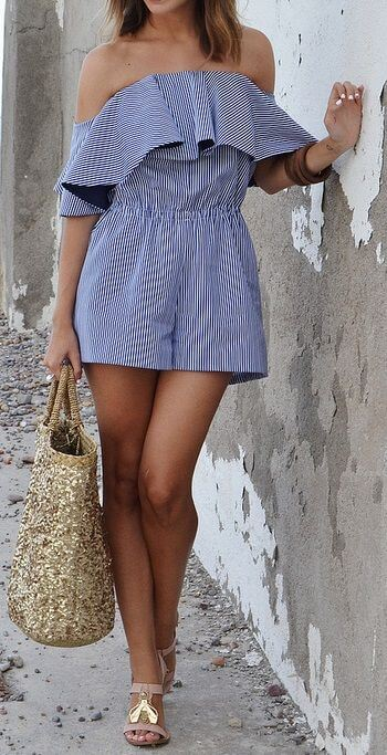 Stylish woman in striped romper and gold beach bag. Live la dolce vita in this holiday-inspired look.