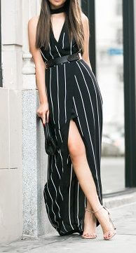 Stylish woman on the street in long black striped dress. A daring thigh-high slit adds some drama to this classy look.