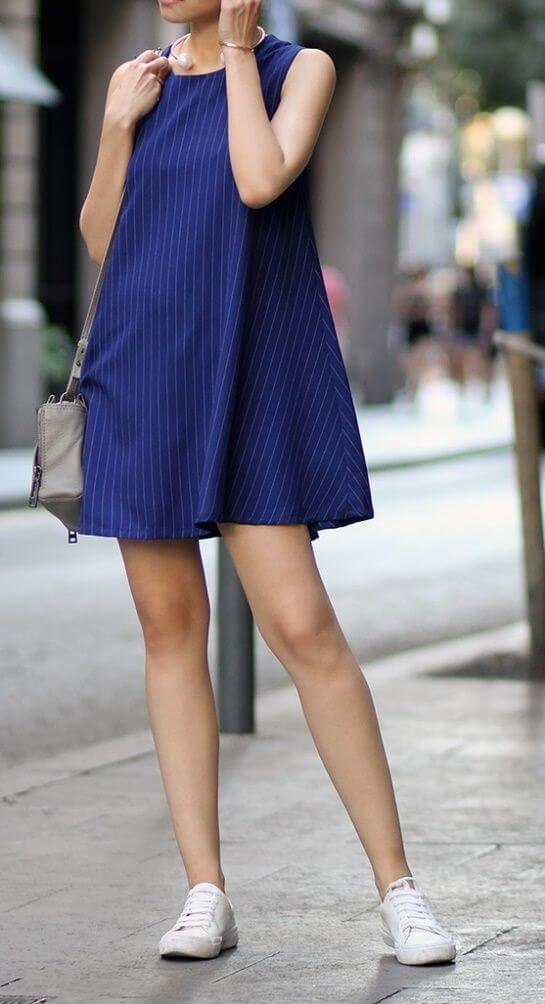 Stylish woman on the street in navy blue striped dress and sneakers. Who would've thought that pinstripes and sneakers would make such a winning team?