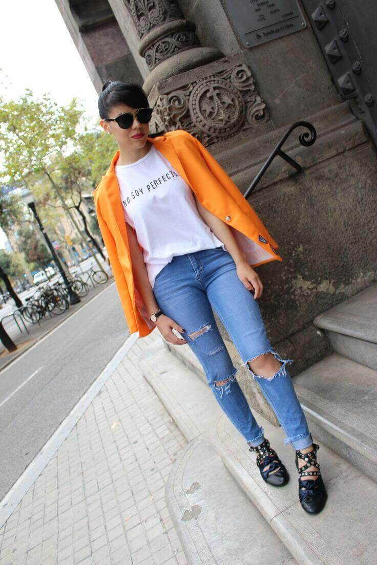 Orange blazer creates a vibrant expression to otherwise quite a usual look. The blazer adds charm to torn blue jeans worn with a white tee.