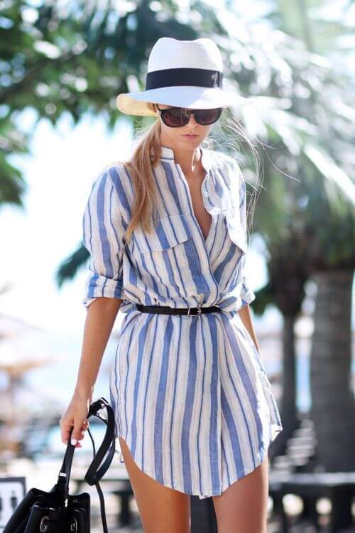 Trendy blonde in striped shirtdress and Panama hat. Holiday fashion is all about simple stripes with the right mix of accessories.