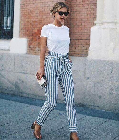 Trendy blonde in white T-shirt and striped pants. A simple white T-shirt is elegant and striking when worn with classic stripes.
