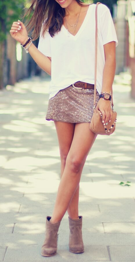 Trendy brunette is wearing a sequined mini skirt and a white cotton T-shirt. Play around with fun elements in your wardrobe like sequins, suede, and leather.