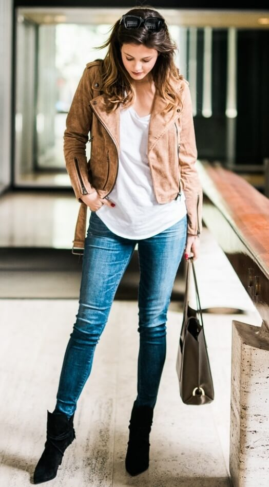 Trendy brunette is wearing skinny blue jeans and a brown suede moto jacket. Casual and chic, a suede moto jacket is early spring's most necessary style item.