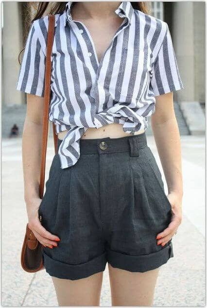 Trendy woman in gray high-waisted shorts and striped shirt. Go back to school in gray pleated shorts and a cheeky knotted striped shirt.