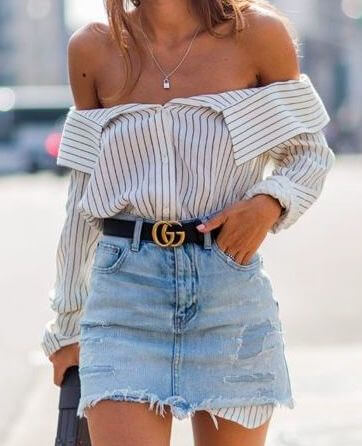Trendy woman in off-the-shoulder striped shirt and denim skirt. Wear a men's shirt in the season's trendiest style: off-the-shoulder, and paired with denim.