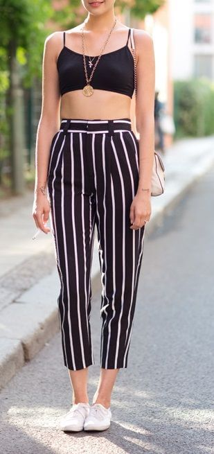 Trendy woman in striped pants and black crop top. Get that sporty effect with vertical stripes and a matching black bralet.