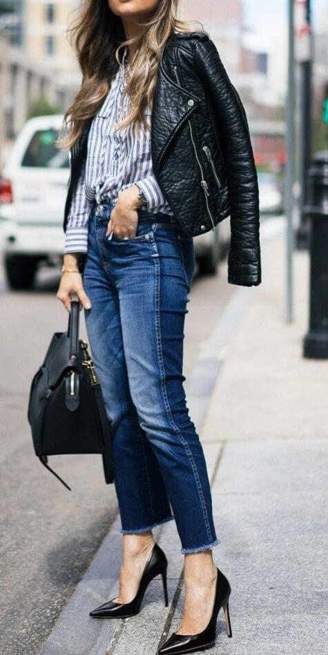 Trendy woman on the sidewalk in jeans, striped shirt and leather jacket. Match vertical stripes with blue jeans and faux leather for fun, edgy fashion.
