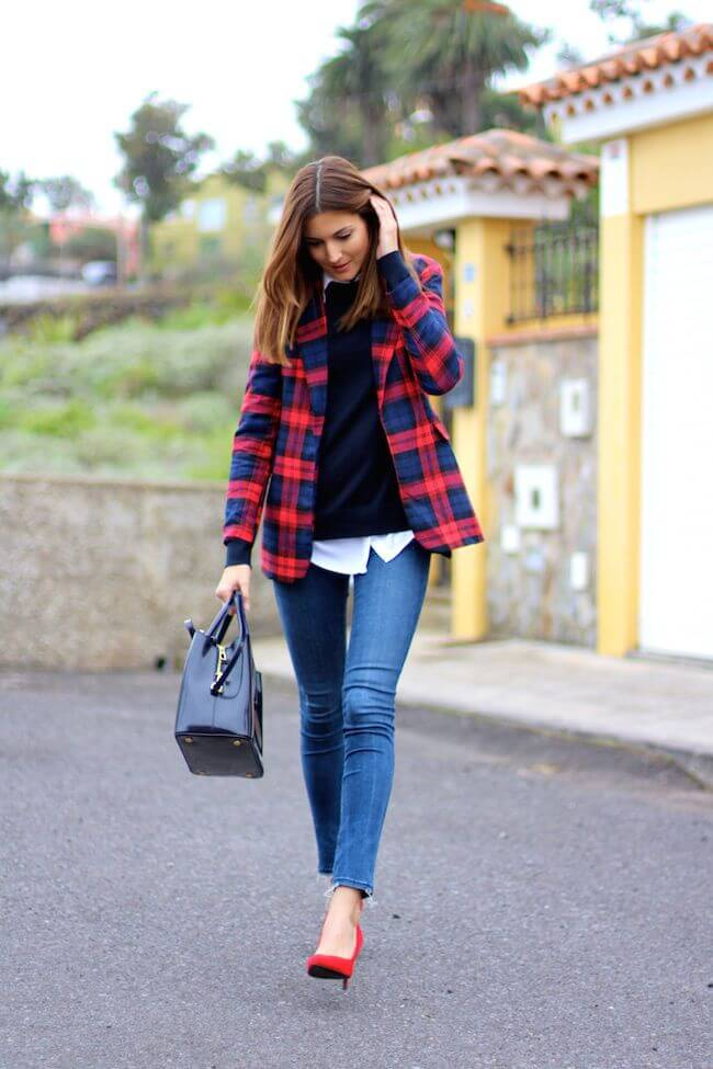 Woman with a casual outfit made of jeans, sweater, and a bright tartan blazer