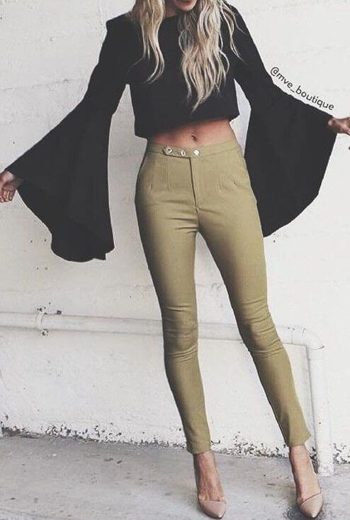 Fashionable woman in olive green pants and black bell sleeve top. A classic combination of black and olive green celebrates the popular bell sleeve trend.