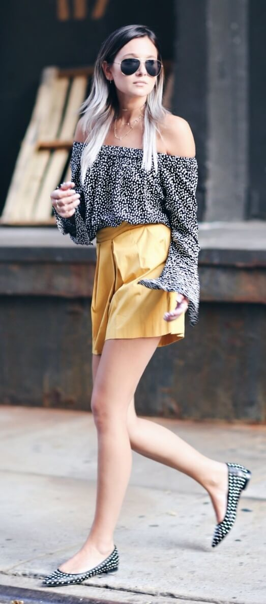 An edgy woman in the city is wearing yellow shorts and an off-the-shoulder top. This modern city look puts a preppy spin on the off-the-shoulder trend.