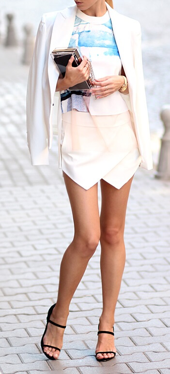 Stylish woman is wearing an asymmetrical wrap skirt and white blazer. Give the boys a run for their money in this feminine-inspired power suit.