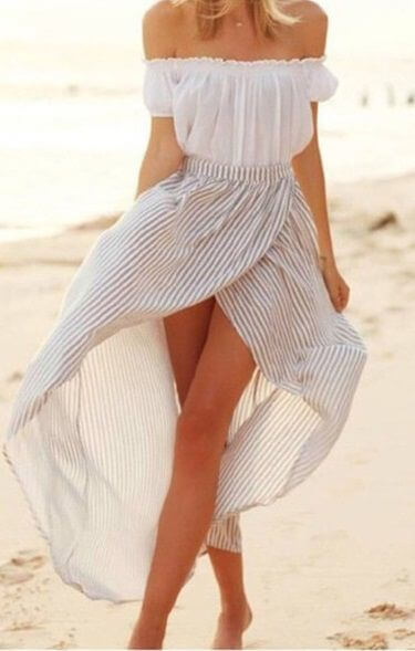 Woman on the beach in white off-the-shoulder top and striped wrap skirt. A striped wrap maxi skirt will get you into the holiday spirit.