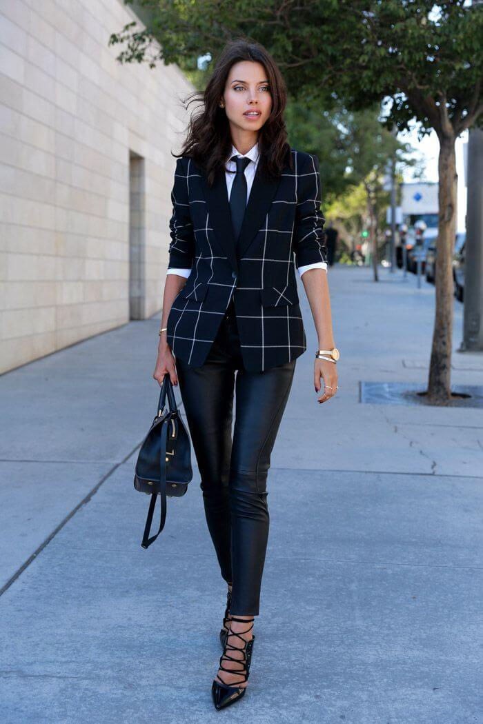 Woman on the sidewalk wearing leather leggings, white shirt with tie and a buttoned blazer