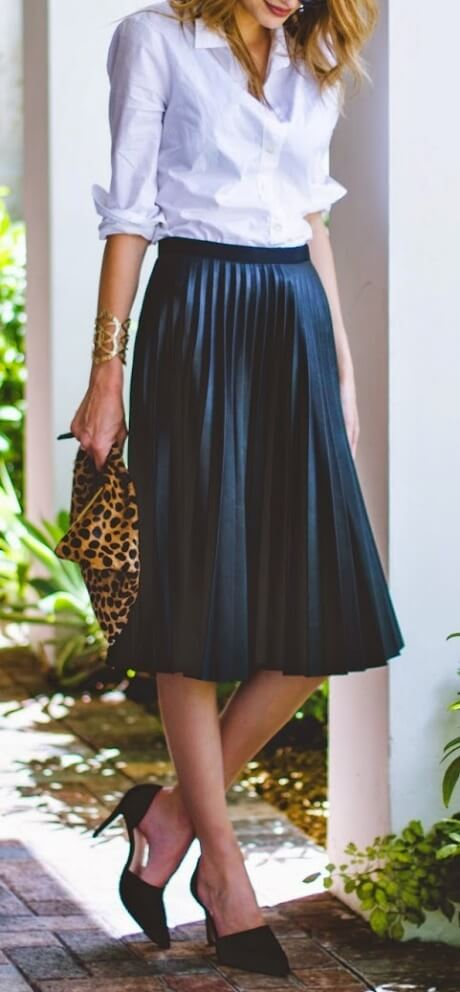 Woman wearing a pleated faux leather midi skirt and button-down blouse. For a classy do, make a pleated midi skirt your first choice this season.