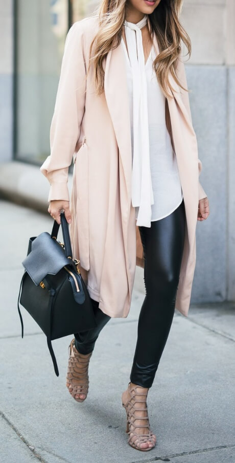 Woman on the sidewalk is wearing black leather leggings and a pink duster jacket. Trust black leather to add edge to the super-girly pink duster jacket.