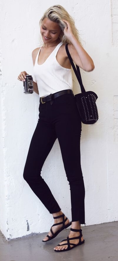 Woman is wearing black skinny jeans and a white vest. This sort of basic outfit works perfectly as a daytime uniform for busy women on the go.