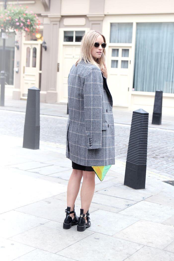 Woman with simple black dress, retro ankle boots with cut-out details and long retro tartan blazer