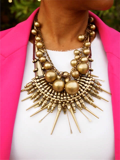 A mix of golden colored necklaces combined with a white top and a pink blazer