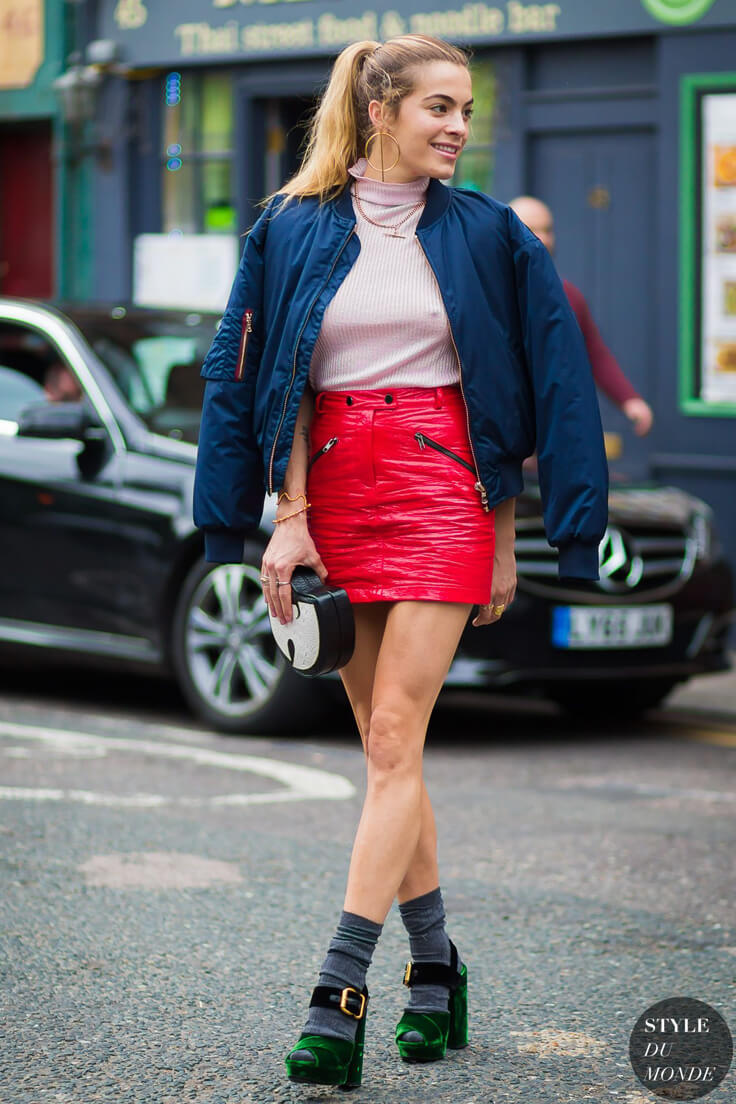 Blonde in a blue bomber jacket, pink turtleneck, red leather mini skirt and gray socks under green velvet block heel sandals with ankle strap.