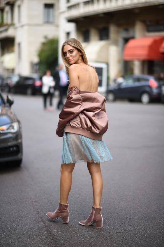 Chiara Ferragni shines in blue mini dress, Acne Studios bomber jacket, velvet ankle boots and clear lens glasses.