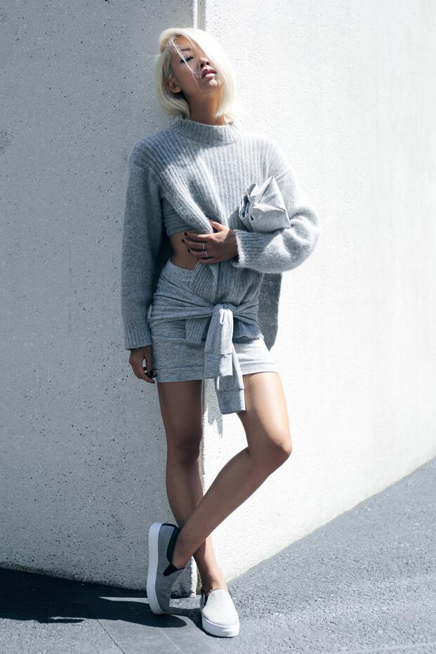 Vanessa Hong pairs together gray knit pullover, gray stretchy mini skirt with tied belt straps and gray slip on sneakers