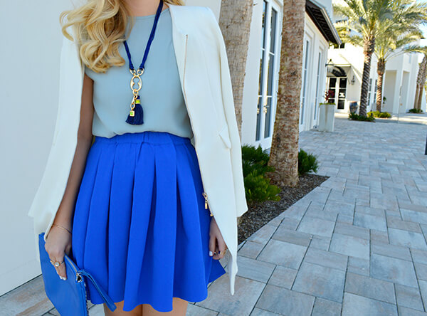Tassel detail necklace in blue adding some chic fill to a spring outfit of skirt and beige blazer