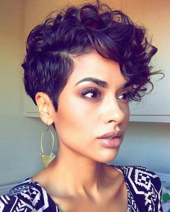 Less drastic than an undercut but undoubtedly just as stylish, the faux hawk is a style curlies can pull off with ease. The model's dark brown tresses fall just below her eye on one side of the part while the other side is cropped to just a few inches.