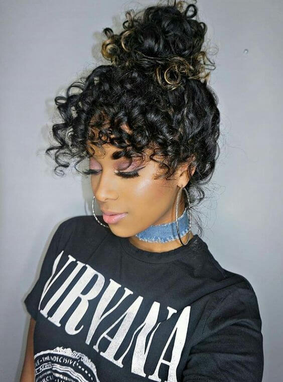 Gorgeous black to gold curly ombre hair is thrown up in a bun, letting us admire the eye-grazing curly bangs.