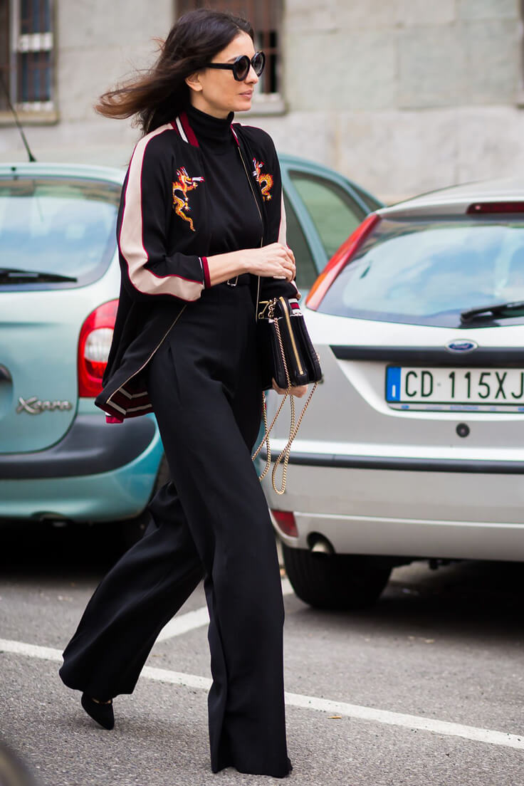 Leila Yavari is wearing black turtleneck, black wide-leg trousers, black satin bomber jacket and black heels during Milan Fashion Week