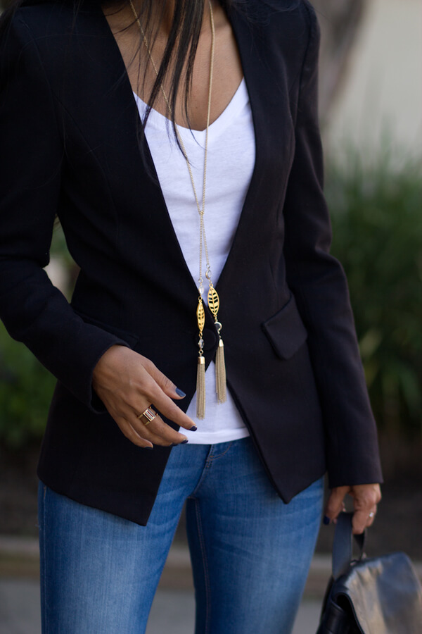 Black one-button blazer with a long tassel detail necklace lengthening the silhouette