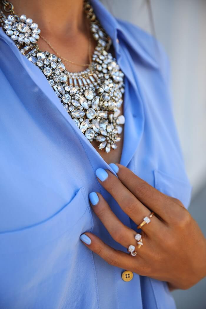 Blue shirt in the company of massive necklace with white rhinestones