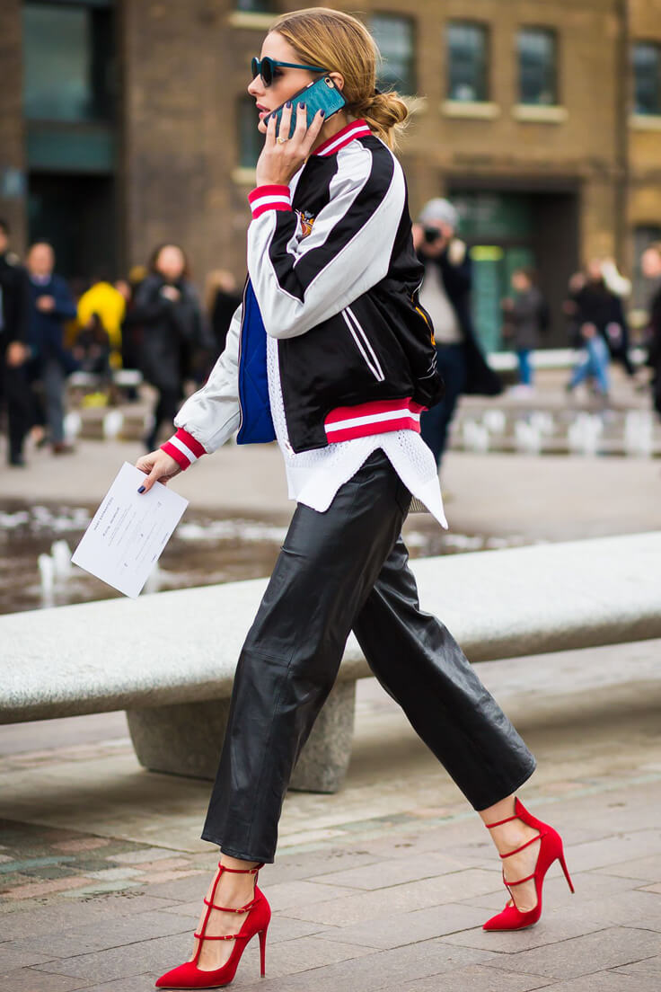 Olivia Palermo dressed in silk bomber jacket, black leather pants, red suede pumps.