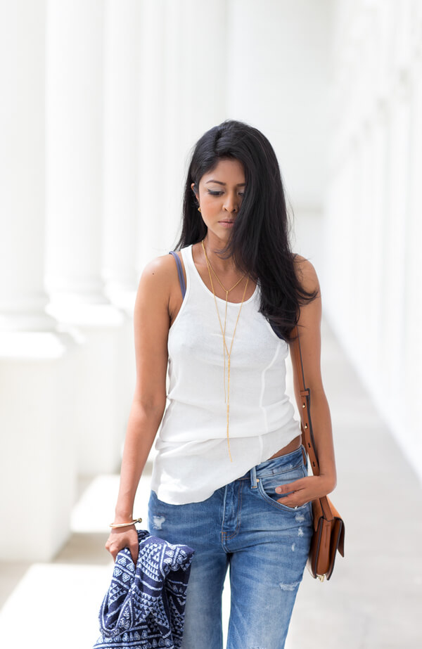 Dark hair girl with white tank top, blue jeans and simple long golden necklace