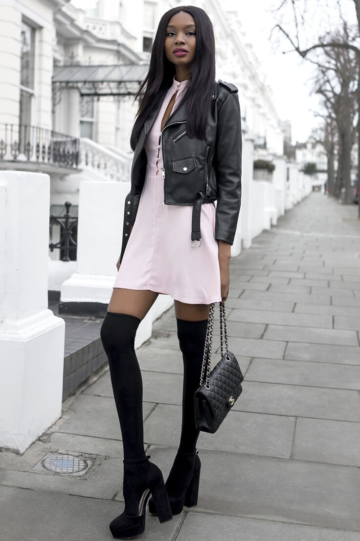 Stylish brunette wearing the black leather jacket over high neck dress with buttons, black thigh high socks with black suede platform sandals