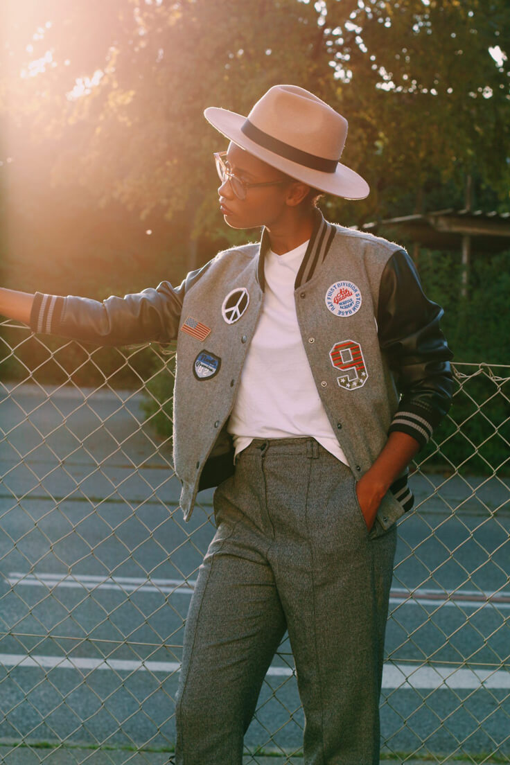 Miss the 80's vibes? Check this look with patch bomber jacket, gray cigarette trousers, white t-shirt, and fedora hat